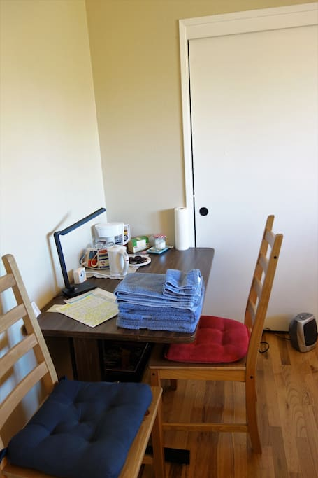 Guest master bedroom: a big desk, desk lamp, 2 chairs, an electric tea kettle, water filter, glasses, tea bags, instant coffee sticks, sugar, teaspoons, cups, some complimentary cookies, plates, tissues, a space heater, guest set of towels
