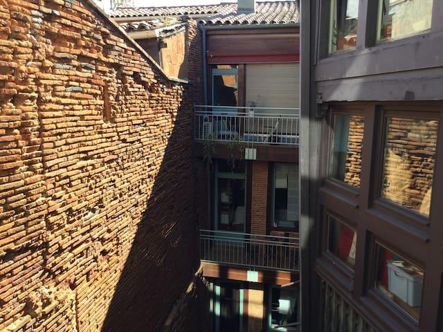 Vue chambre 2, est, mur de briques et escalier en bois