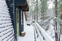 Side of the cabin looking back into the woods after a light snow storm.