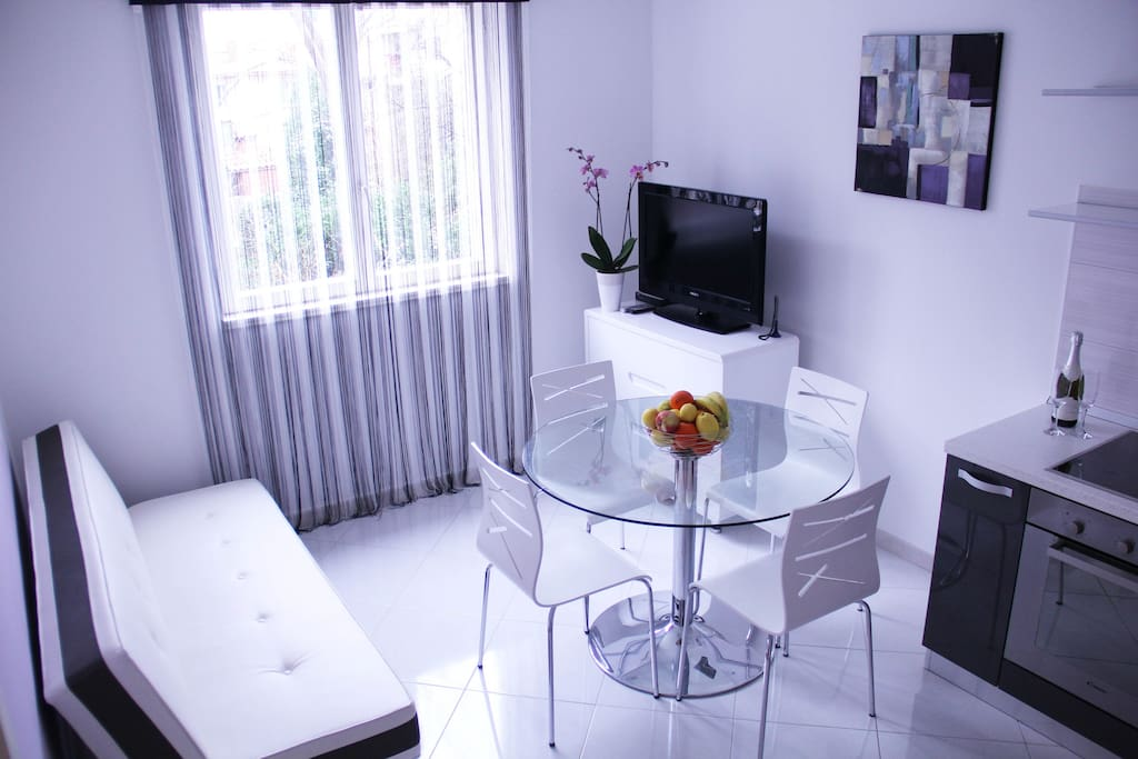 Living room with sofa, TV,  kitchen and table for four