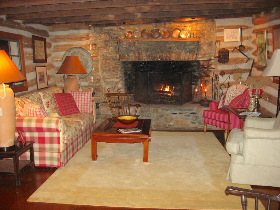 Cozy but spacious log living room, huge original fireplace,lots of wood.