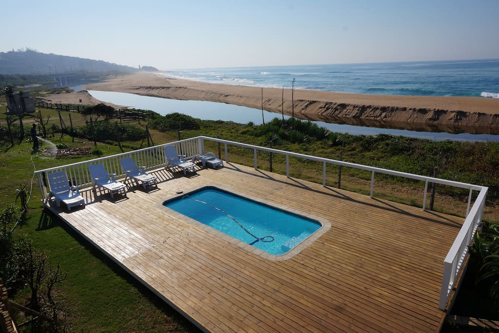 The house with swimming pool and large decks and balconies is directly on the beach