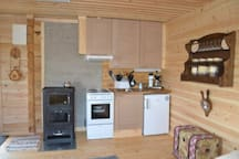The kitchen include fridge, oven, coffeemaker  and cutlery