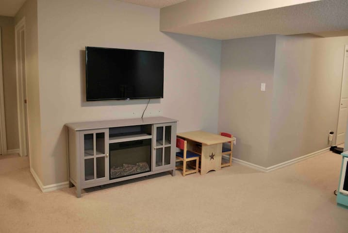 "55"" Roku TV with Netflix, electric fireplace, and children's table"