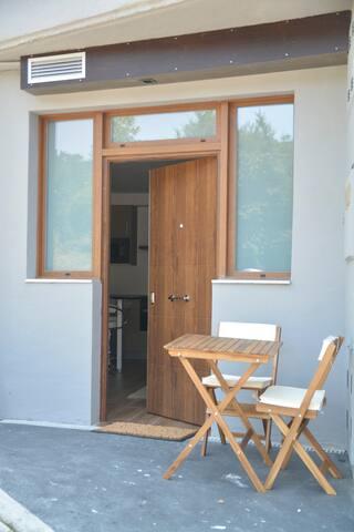 Entrada exterior con mesita y sillas para desayunos o descanso.