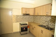 View of the kitchen and the cooking stove. Plenty of kitchenware in the cabinets