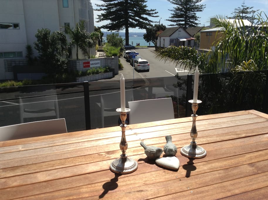 View from beautiful patio that opens off the open plan kitchen dining living area. The beach is close to the pine tree across the road from the house. Tere are changing sheds, a shower and playground there too!