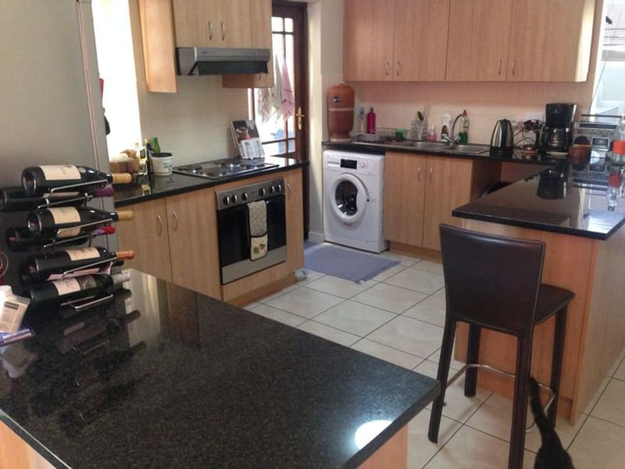 Fully equipped, open-plan kitchen with plenty of surface space, a washing machine and a tumble-drier.