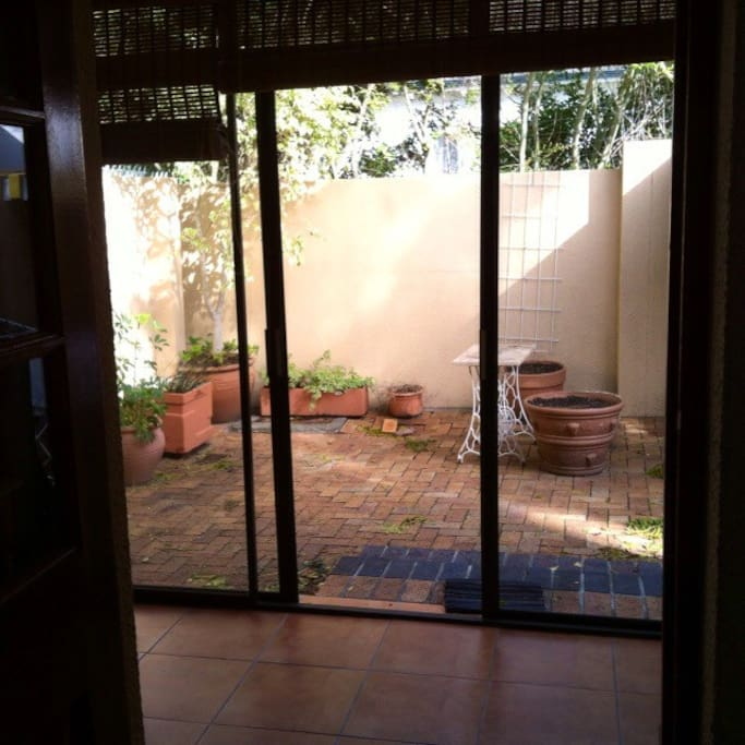 Enclosed patio with desk, built-in fireplace/bbq/braai overlooking semi-private courtyard.