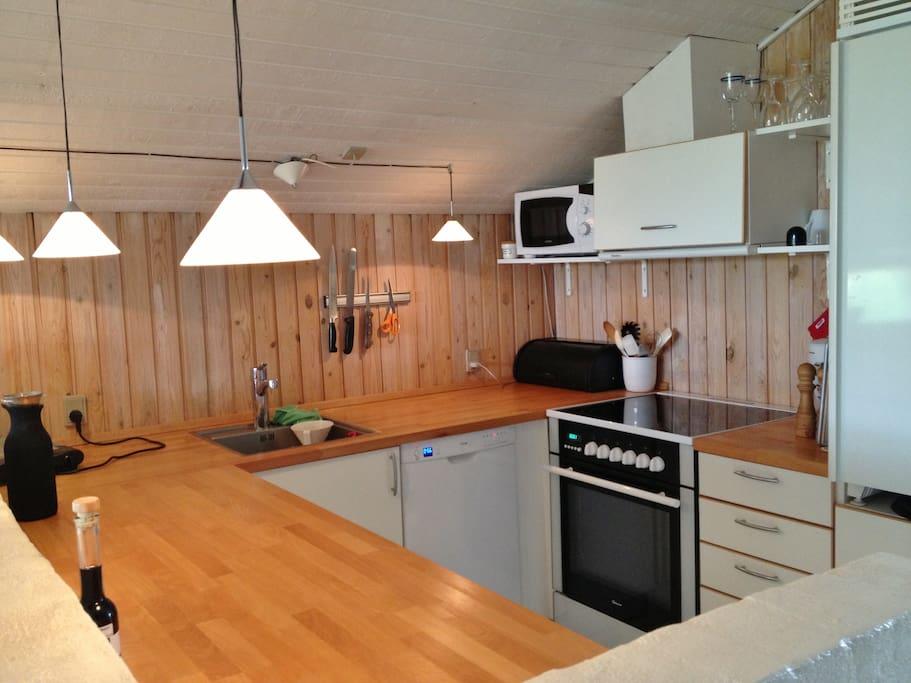 Veludstyret køkken med opvaskemaskine og mikrobølgeovn.