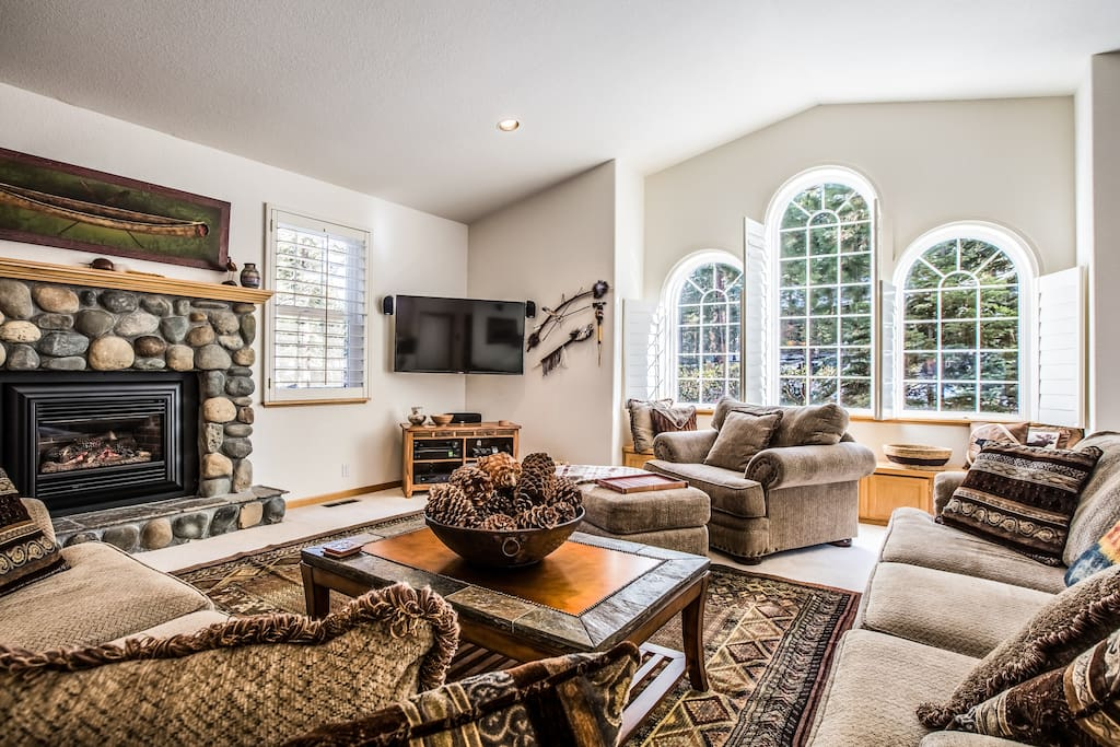 Tall windows and rock fireplace and cozy furniture invite comfort in this gorgeous living room