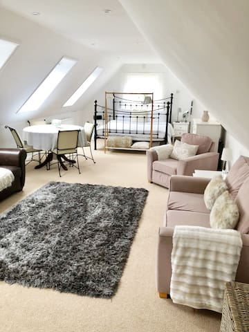 open plan living space, 2 x sofa and 1 armchair, dinging table with 4 chairs and super-king bed at end of room.