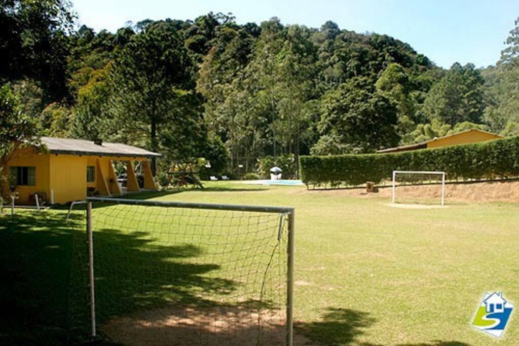 Campo de futebol. À esquerda a casa e ao fundo piscina e salão de festas