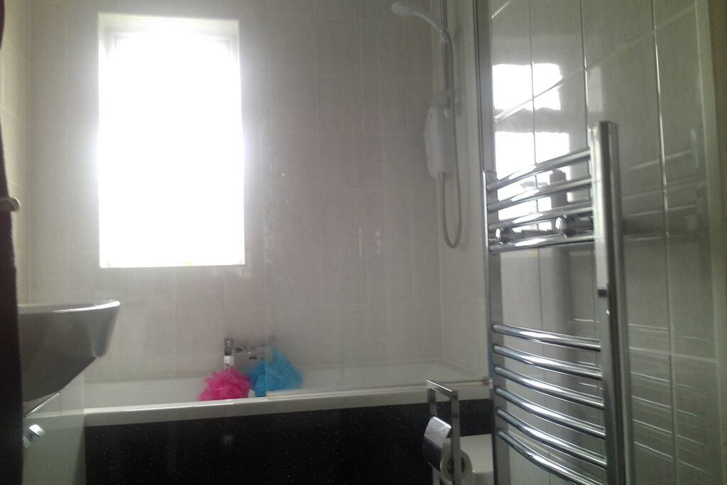 Recently renovated shared bathroom with shower, bath, demister mirror and heated towel rail.