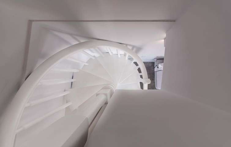 A spiral straicase will lead you to the top level of the residence where the bedroom and bathroom are located