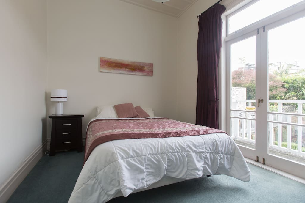 Your room with quality bed and French doors to a small verandah