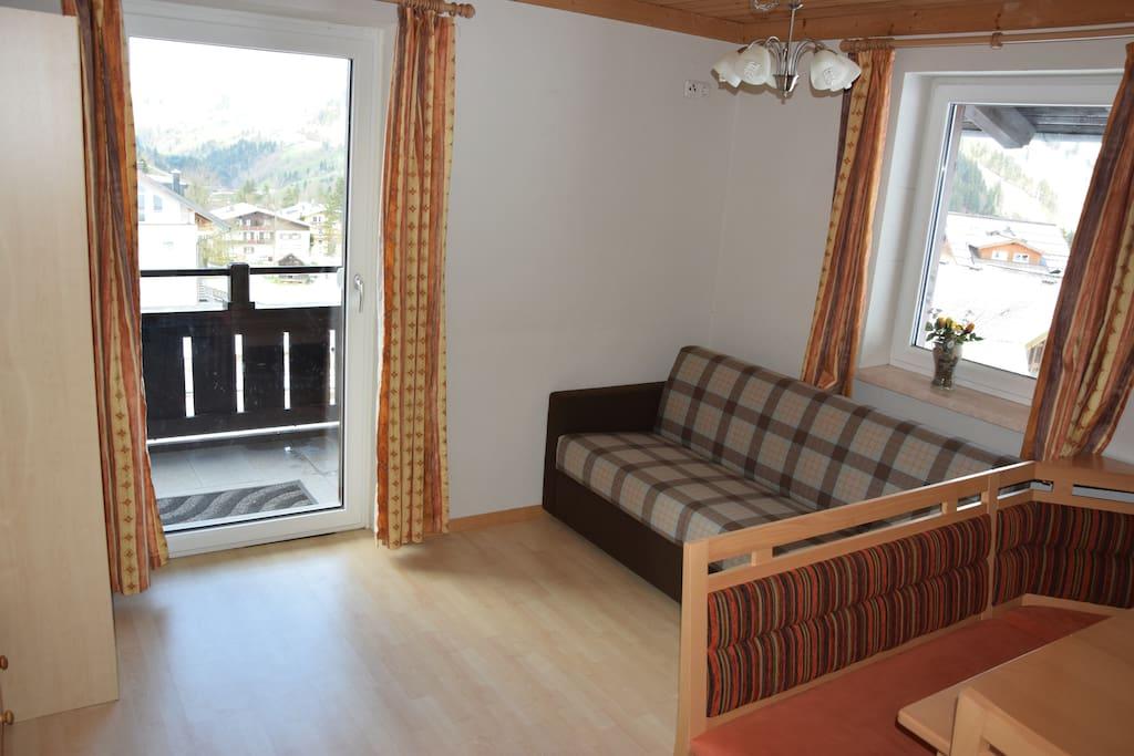 Wohnzimmer mit Balkon und klappbarem Sofa