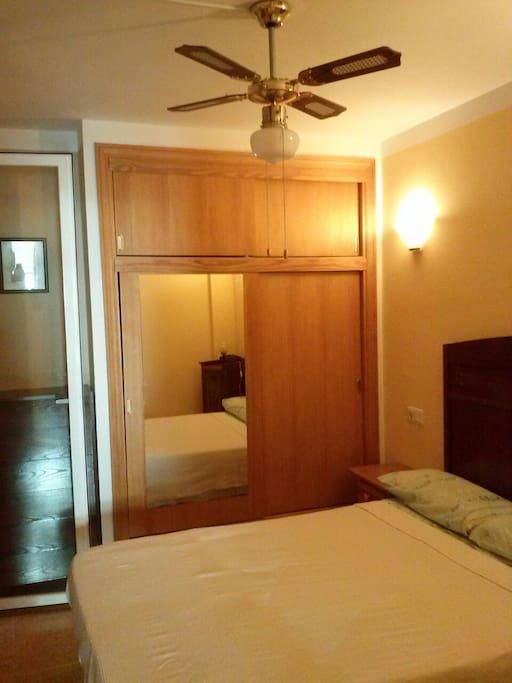 Habitacion con armario y ventilador de techo.