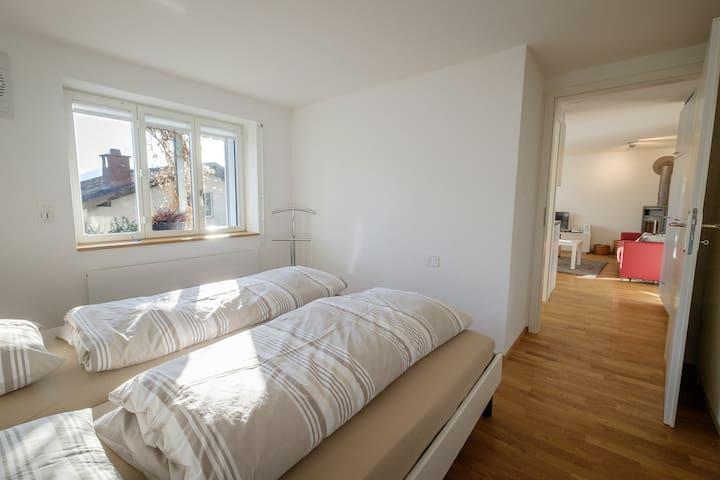 Helles Schlafzimmer mit 2 Betten, 1 Kinderbettchen und mit grossem Kleiderschrank.