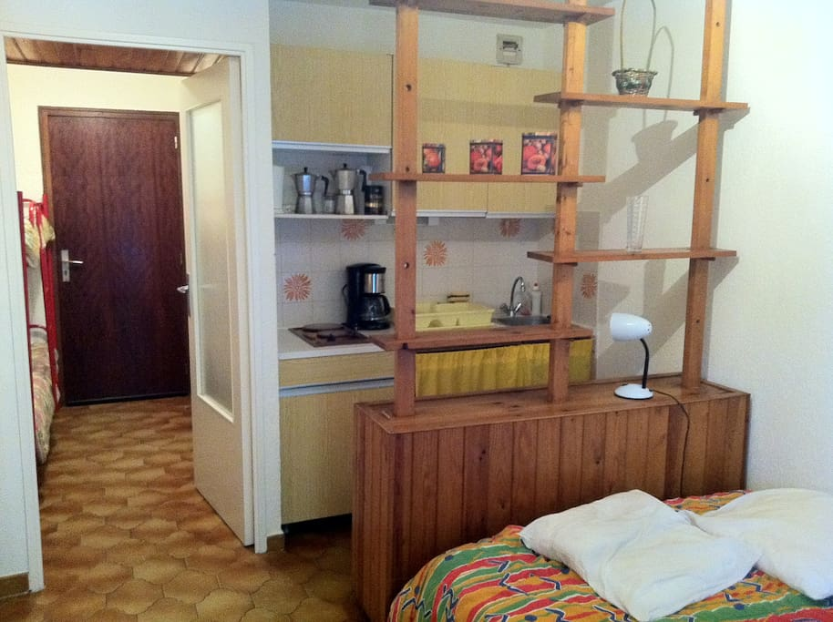 le sejour avec son canapé lit 2 places, suivi du coin cuisine, et dans l'entrée 2 lits superposés