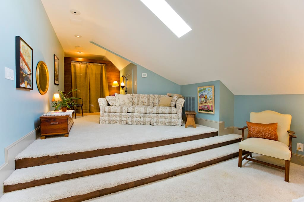 Step up to sitting area with large comfortable sofa and entrance to walk-in closet