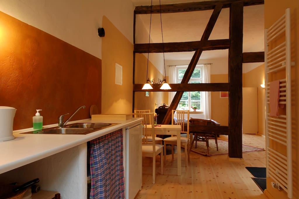 Küche und Esstisch sind nur durch Balken vom Wohnraum getrennt