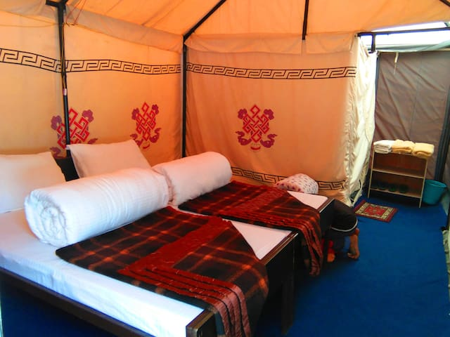 With three layered insulated mat floored room with attached bathroom,6 to 6.30 feet adjustable cot,6 ' mattress,400 GSM quilt & pillow,100% woolen blankets,you can have a good sleep surrounded by buddhist lucky signs on the tent inner walls.