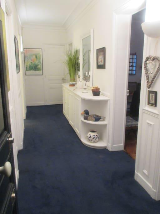 Entrée blanche et bleue desservant les pièces de l'appartement