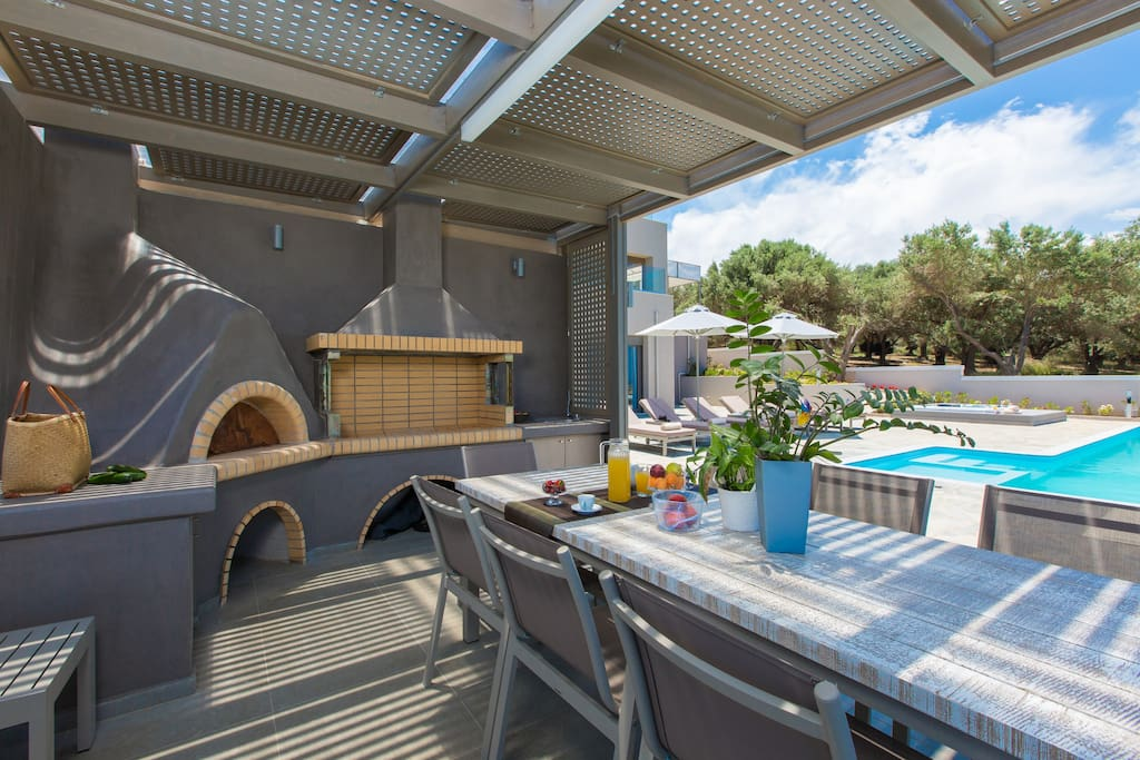 Fully equipped barbecue with wood oven, sink and dining area under the pergola.