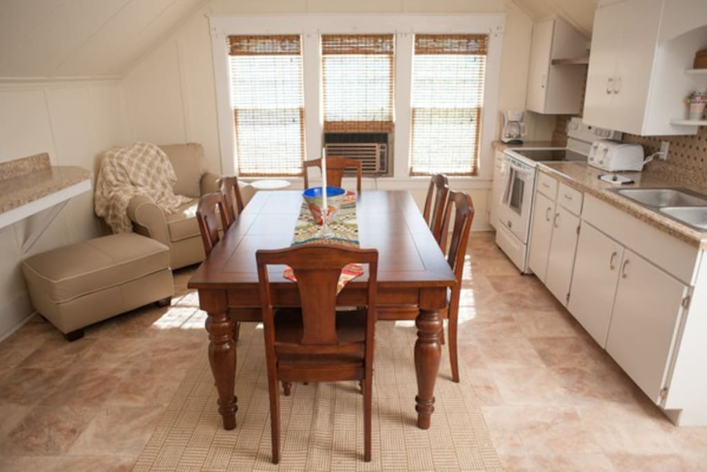 The kitchen features a breakfast bar, table seating, and full appliances.