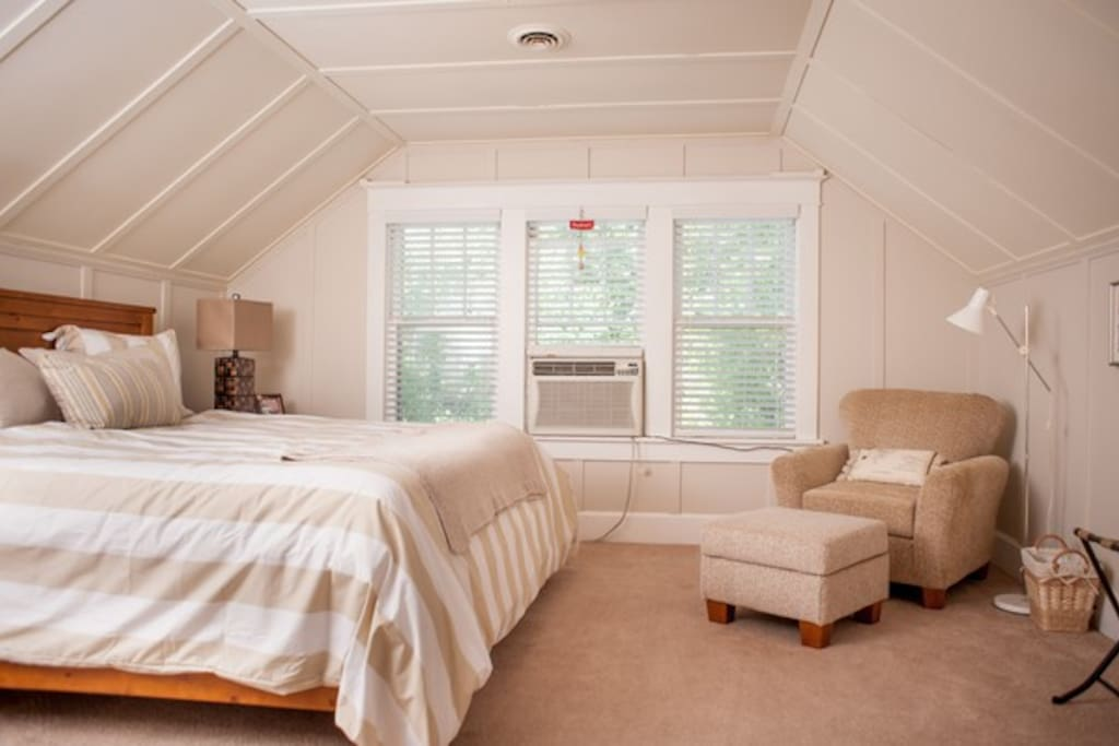 This bedroom includes a vitage luggage rack, king size bed and washed linen sheets.