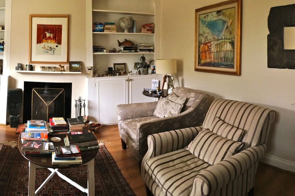 Guest sitting room with sofa and chairs, books and maps and a wood burner for those cold winter days and nights.