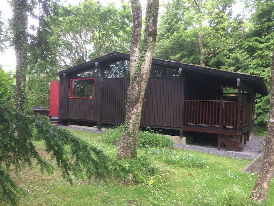 Cabin Ishbel nestled in the trees at the edge of Penlan Holiday Village.