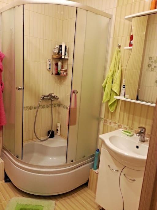 Cozy bathroom with towels, shampoo and shower gel.