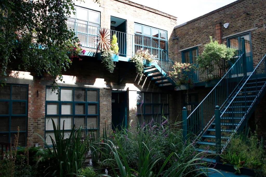 The courtyard of the warehouse development with garden and modern fountain bringing the sound of water to the urban jungle