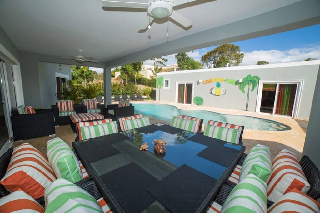 CASA COCO-PINA covered terrace houses an over sized custom dining table & 8 chairs as well as custom entertainment seating