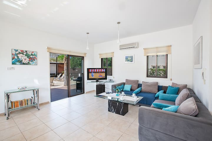 Living room with comfortable seating area, widescreen TV and patio doors leading to the pool and garden