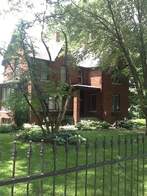 Large brick two story with a black iron fence and archway