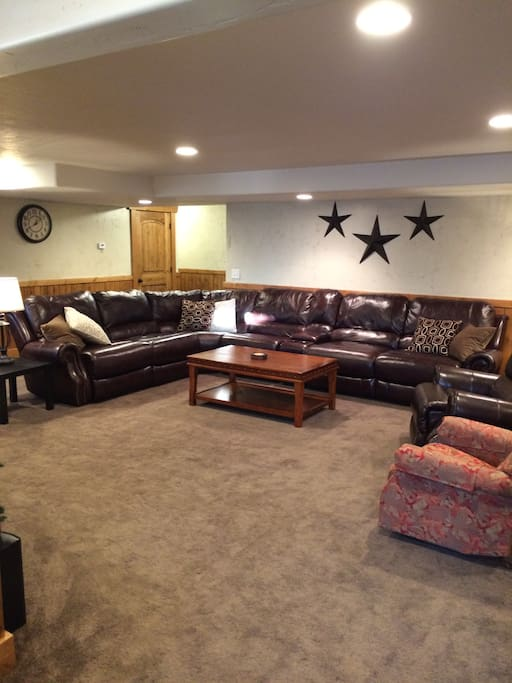 Very large family room, with plenty of comfortable seating on leather sectional with recliners.