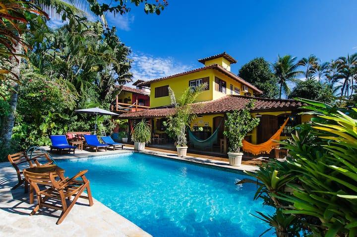 Suíte e jardim tropical com piscina