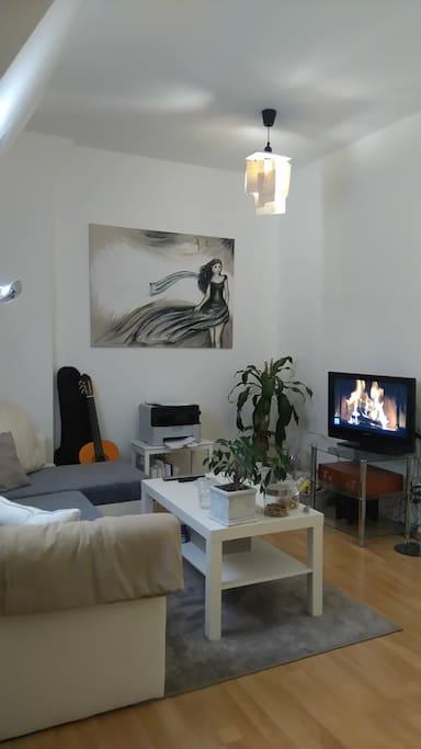 Die Couchecke mit Fernseher. Die Couch ist Ausziehbar und eine zweite Decke mit Bettwäsche ist vorhanden.