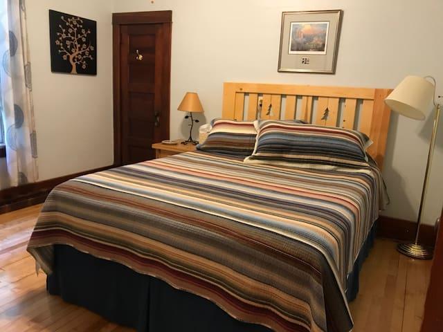 Bedroom #1, first floor, queen bed, dresser, night stand, reading lamp, closet.