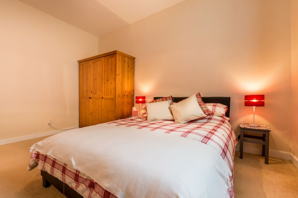 The bedroom has a comfortable double bed and ample storage.