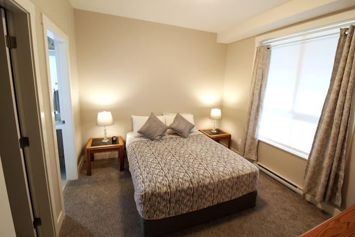Master bedroom with queen sized bed, en suite bathroom and walk in closet.