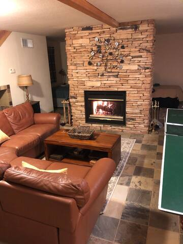 """Relax on the leather sectional sofa, watch the 65"""" Roku TV, play ping pong, pool, or take a nap in the semi-private sleeping area behind the fireplace. (candles only in the fireplace, it gets smokey)"""