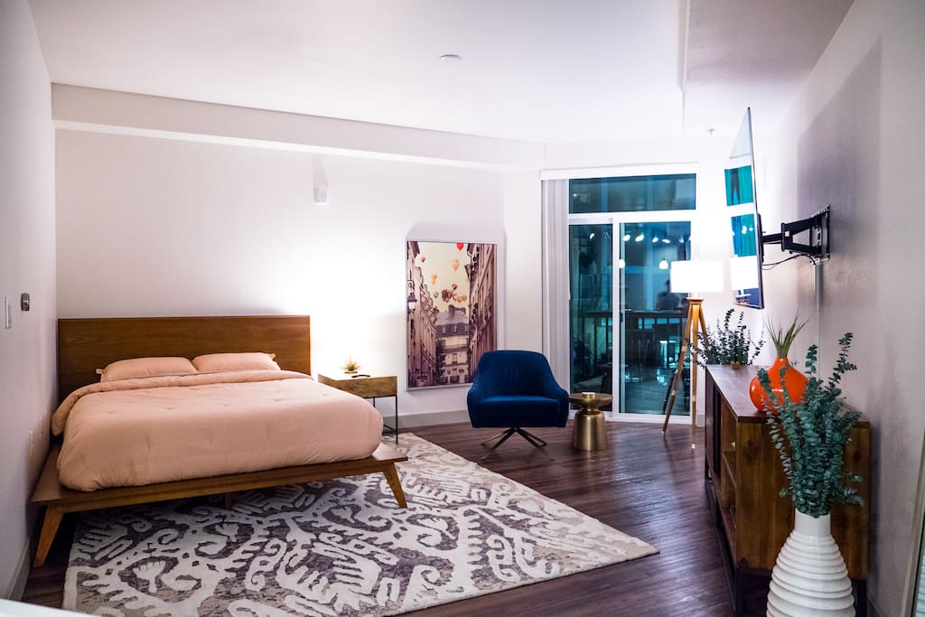 The living space includes a 65inch smart television, accent chair, and a queen size bed with a bed side table and a window view of the pool area, note this studio does not have a balcony.