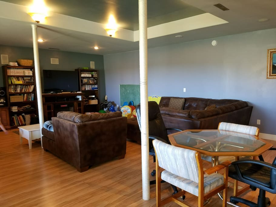 Living room area with large tv, couches that seat 10 and can be used to sleep guests. TV has Netflix and is a 3D TV.