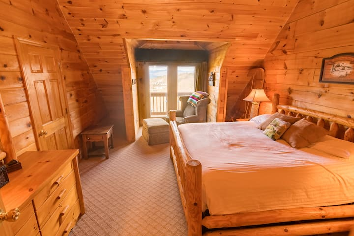 Master bedroom featuring king size log bed upstairs, with views on both sides of the home and a private bath.