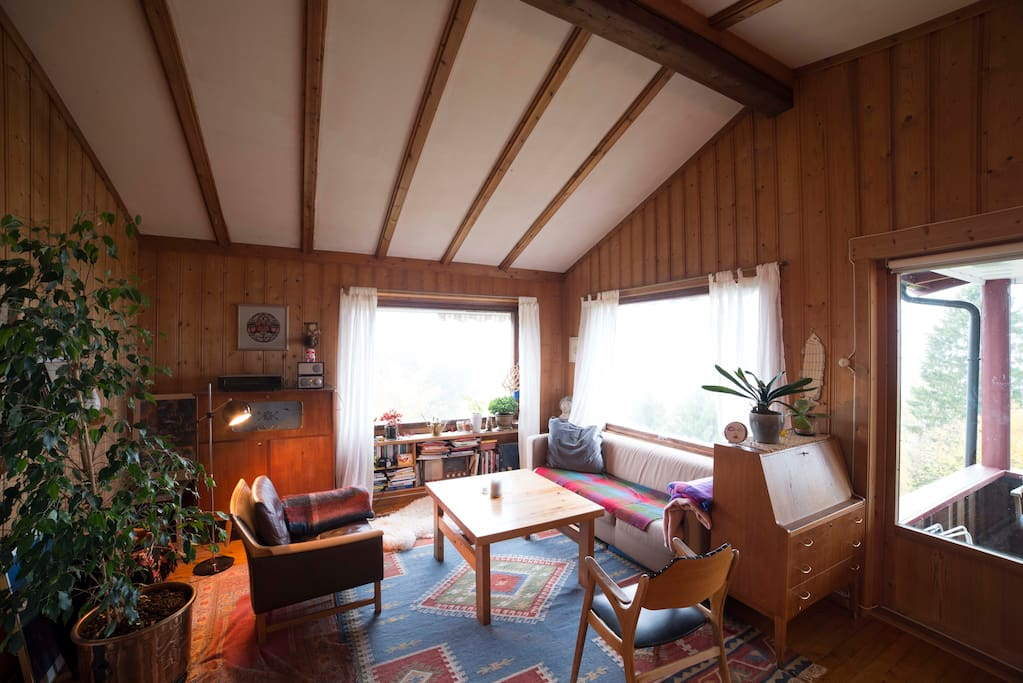 The living room has a high ceiling and a 180 degree view of the fjord through the windows.