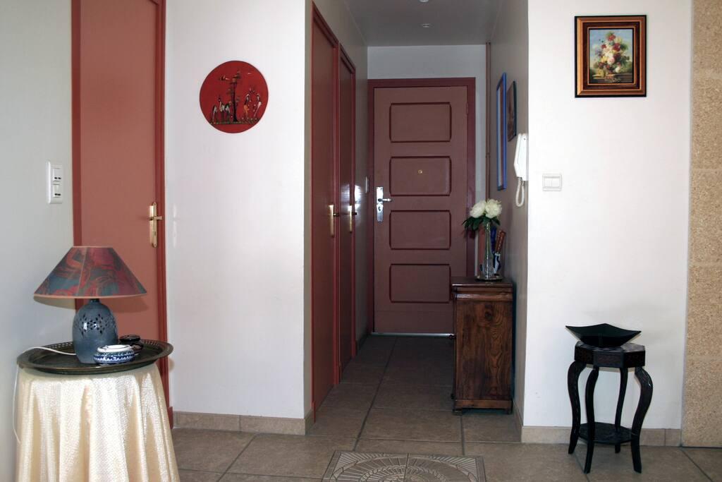 Le couloir de l'entrée avec la porte des toilettes et la porte de la salle d'eau